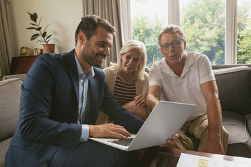 Active senior couple discussing with real estate agent over laptop in living room