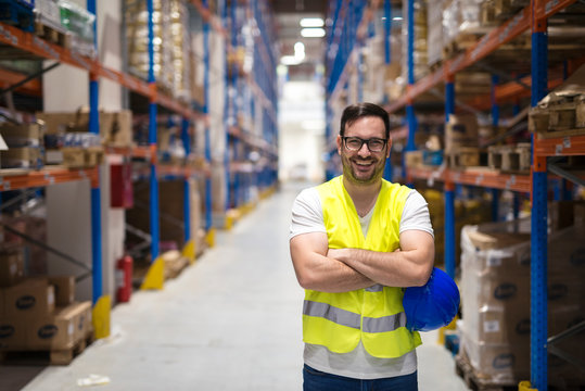 Portrait of middle aged warehouse worker standing in large warehouse distribution center with arms crossed. In background shelves with goods.