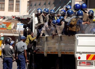 Riot police detain suspected opposition Movement for Democratic Change (MDC) supporters during clashes after police banned planned protests over austerity and rising living costs called by the opposition Movement for Democratic Change (MDC) party in Harare