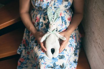 View from above of pregnant mother in flowery dress sitting on stairs, embracing belly and holding cute toy bunny for future child. Mother waiting for baby. Concept of anticipation.