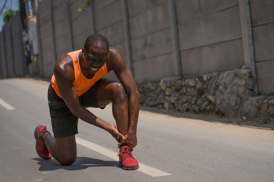young athletic and fit black afro American runner in pain holding his ankle after suffering medical problem with injuried tendon or ligament during urban running workout