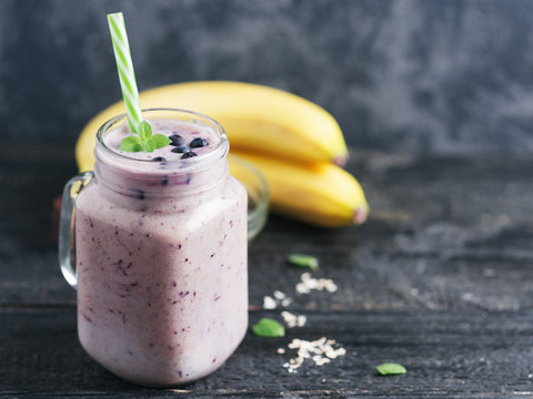 A jar of dark smoothie with blueberries and banana on a wooden table