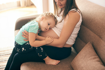 Side view of cute girl embracing big belly of pregnant mother. Happy woman and child sitting together on sofa and expecting little baby. Concept of parental love and pregnancy.