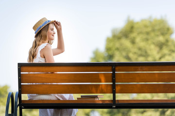 Wall Mural - side view of beautiful girl in white dress touching straw hat and smiling while sitting on bench and looking away