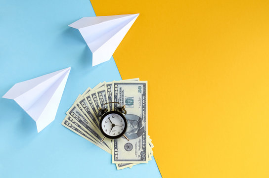 White paper planes, alarm clock and money on blue and yellow background composition.
