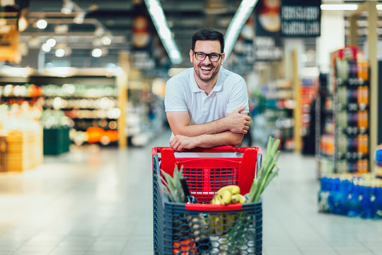 Handsome man shopping in supermarket pushing trolley and smilling.
