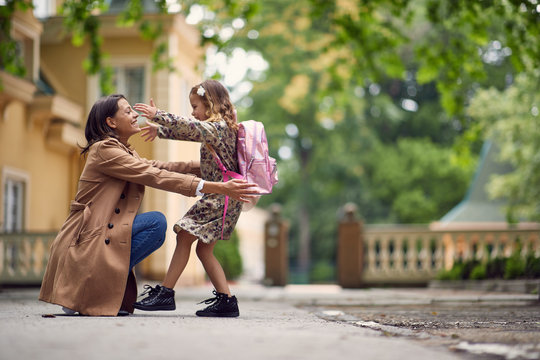 businessmom hugging her little gilr after school