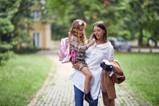 busy mom walking with her daughter after school