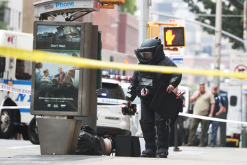 A NYPD Bomb Squad officer investigates suspicious packages near West 16th Street and Seventh Avenue as police were investigating suspicious packages in Manhattan