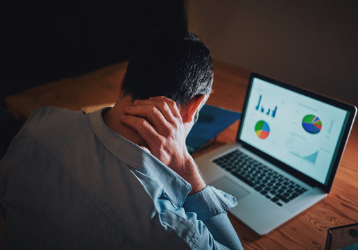 Man working on business project using laptop suffering from neck pain