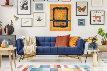Navy blue couch with bright blanket and two cushions standing in