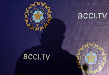 The shadow of a man falls on a backdrop with the logo of the India's cricket board BCCI before the start of a news conference to announce its cricket team's coach, in Mumbai,