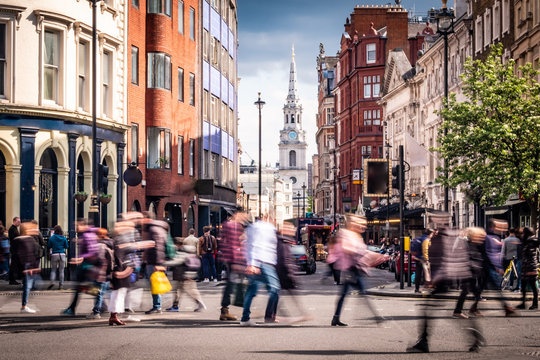 Motion blurred people on busy street in London's West End, UK
