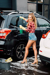 happy girl holding spray bottle and washing car with squeegee