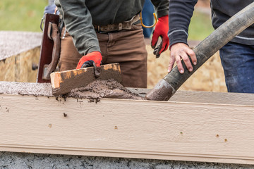 Construction Workers Pouring And Leveling Wet Cement Into Wood Framing