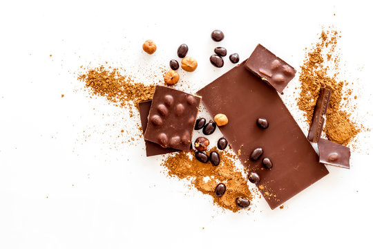 Chocolate bars and nuts on white table background top view