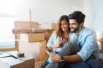 Young couple in love shopping online in new family home. Consumerism, love, dating, lifestyle concept  - Stock Image