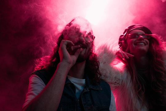 man smoking marijuana joint near smiling girl in nightclub