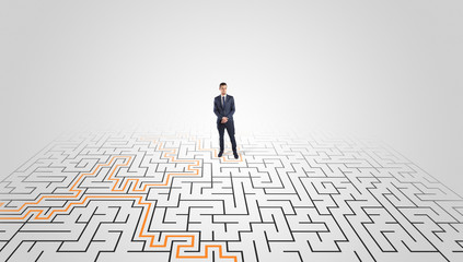 Young entrepreneur standing in a middle of a labyrinth with the solution