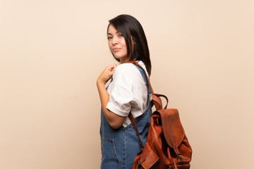 Young Mexican woman over isolated background with backpack