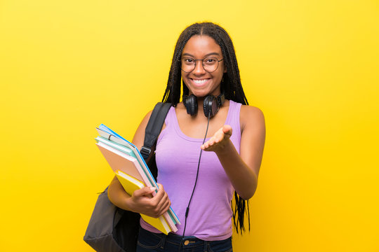African American teenager student girl with long braided hair over isolated yellow wall handshaking after good deal
