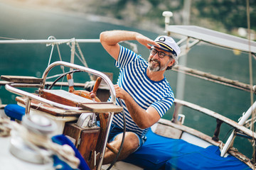 Mature man standing at helm of sailboat out at sea on a sunny afternoon.
