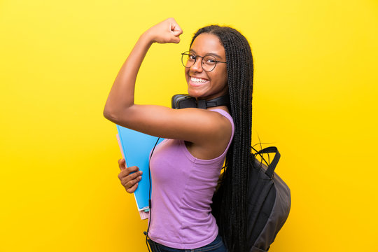 African American teenager student girl with long braided hair over isolated yellow wall making strong gesture