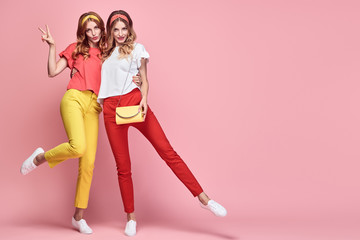 Two Lovable embracing fashionable woman sisters having fun in Trendy summer outfit. Studio shot of slim friends with curly hair, smiling on pink background. Cheerful happy girl, stylish fashion pants Wall mural