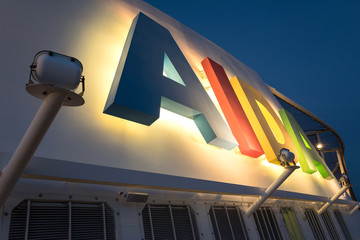 ELBE, GERMANY - June 4, 2017: illuminated AIDA logo at the funnel of cruise ship AIDAsol. AIDA Cruises is one of ten brands owned by Carnival Corp.