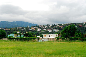 Jamaica, Kingston, view of mountain range covered with foggy sky by built structure on mountain in the foreground