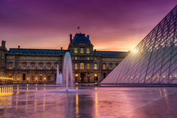 View of famous Louvre Museum with Louvre Pyramid at evening.