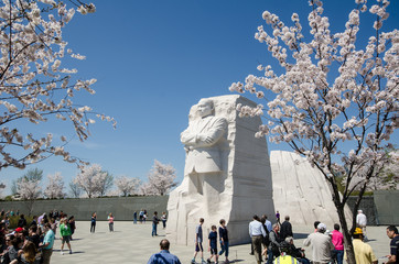 WASHINGTON, DC - APRIL 10, 2019: Tourists crowds gather around the Martin Luther King Jr. Memorial during Cherry Blossom Festival to pay respects and view the monuments