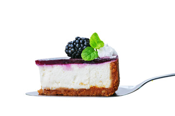 Blackberry cheesecake slice on cake cutter isolated on white. No-bake cheesecake with graham cracker crust, cream cheese filling and blackberry jelly, decorated with whipped cream.