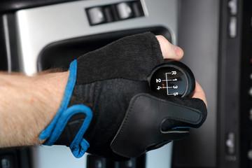 Dłoń w rękawiczce na dźwigni zmiany biegów w samochodzie osobowym, pięcio biegowym.