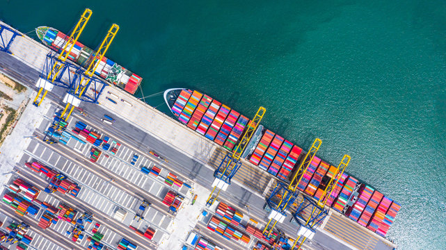 Container cargo ship loading and unloading , Aerial top view of boat business commerce logistic commercial import and export freight  transportation by container cargo ship in open sea.