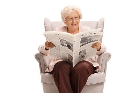 Senior lady sitting in an armchair and reading a newspaper