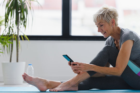 Senior woman using smartphone at home after exercise. The use of technology by the elderly.