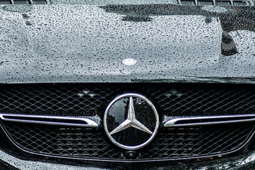 closeup of rain drops on black Mercedes car front parked in the street