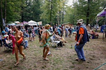 People listen to a band during a celebration of the 50th anniversary of the Woodstock Festival on Max Yasgur's original homestead in Bethel, New York