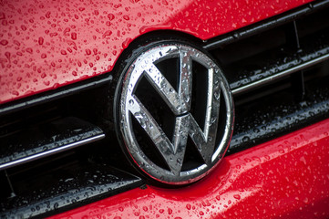 Closeup of rain drops on red Volkswagen polo logo on car front parked in the street