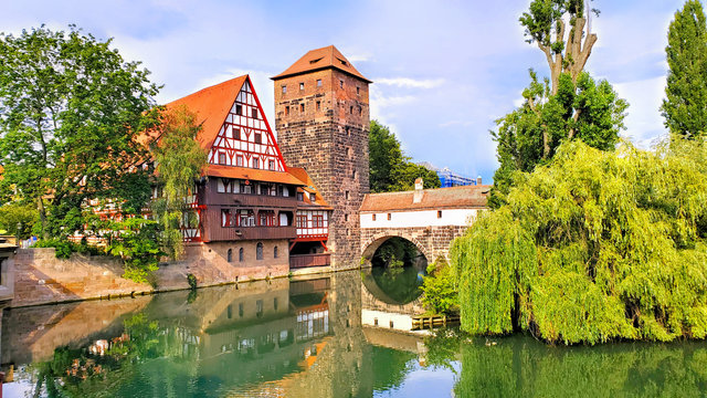 Nuremberg, Germany, beautiful old bridge with medieval tower and half timbered house along the river with reflections