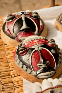Brazil, Amazon, Alter Do Chao. Typical souvenir handicraft masks made on coconut shells and adorned with fish scales, real bones and teeth.