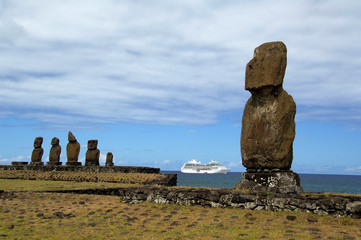 Chile, Easter Island (aka Rapa Nui), Hanga Roa. Traditional Moai with Pacific Princess cruise ship in distance.