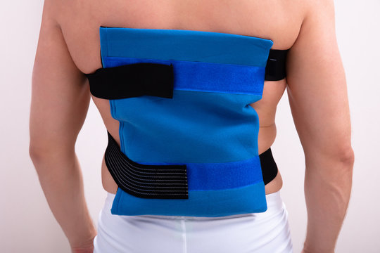 Rear View Of A Man Wearing Ice Pack On Back