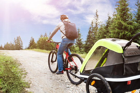 Father With Child In Trailer Riding Mountain Bike