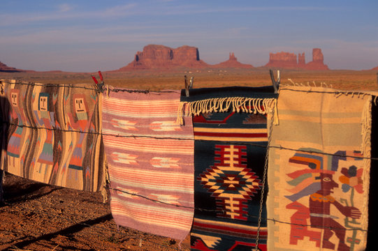 Arizona: Monument Valley, Window Rock, Goulding's Trading Post, Indian blankets displayed on barbed-wire fence with geologic formation in distance.
