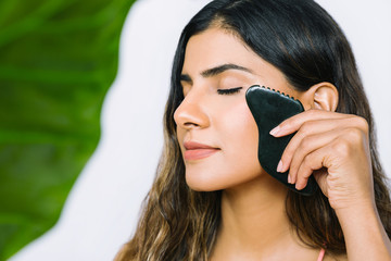 Beautiful Indian woman using obsidian gua sha stone to massage her face - horizontal with green leaf and copy space