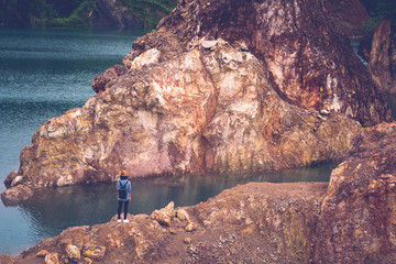Solo teenager traveler walking on rock ground at lake lagoon, Woman tourist travel at lake landscape outdoor background