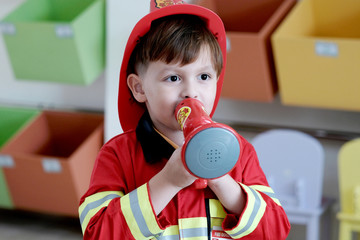 Boy playing as fireman police occupation in kindergarten class, kid occupation, education concept