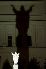 USA, Louisiana, New Orleans. Night scene of illuminated statue of Christ casting a large shadow on church building.